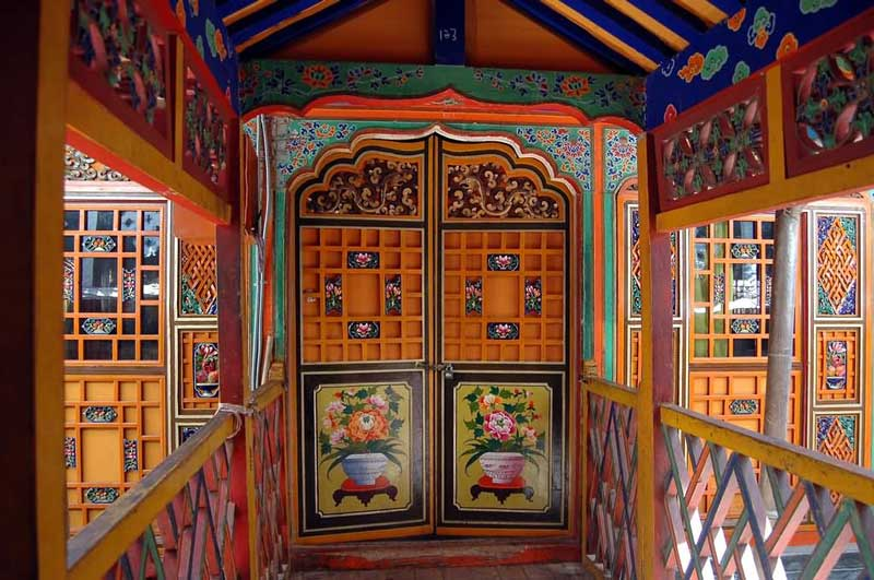 A colourful gate, along with a corridor inside the Potala Palace